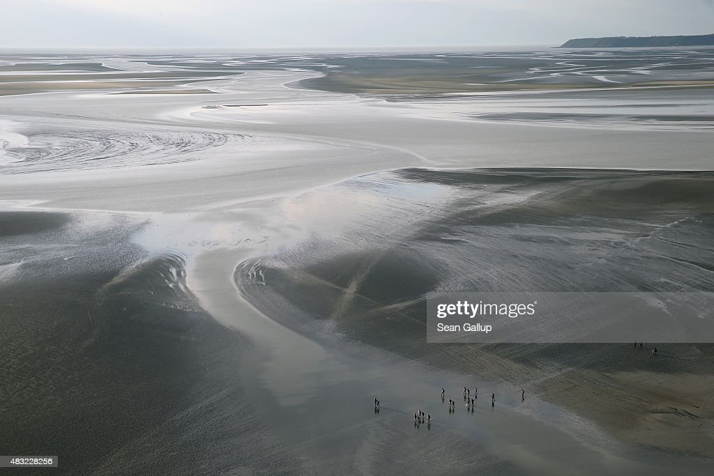 People on a guided tour walk across the mud flats at low tide at sunset on August 5, 2015 near the famous abbey of Mont Saint-Michel, France. The tides recede for miles around the abbey leaving a wide area of mud flats behind that have become a popular tourist desination.