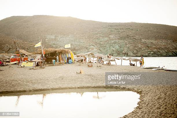 People on a hippie beach with surfers and van in Tinos Island Cyclades Greece