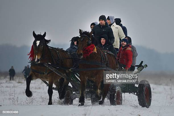 People on a horse carriage take part in the traditional Epiphany celebration in the village of Pietrosani southeast of Sibiu Romania on January 6...