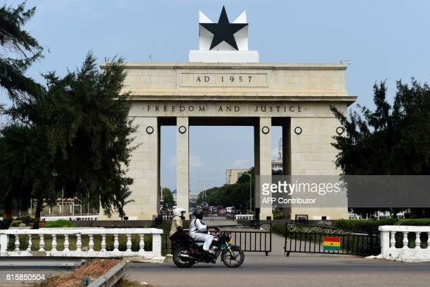 People on a motorcycle drive past the Black Star Gate in Accra on July 14 2017 / AFP PHOTO / PIUS UTOMI EKPEI