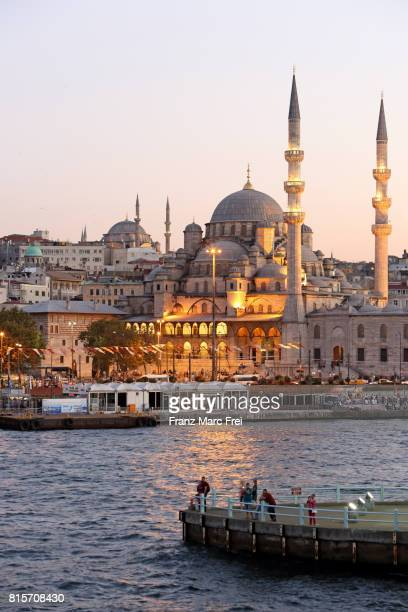 people on a pier of a pillar of galata bridge, in the background yeni-valide mosque and nuruosmaniye mosque, sultanahmet district - istanbul stock pictures, royalty-free photos & images