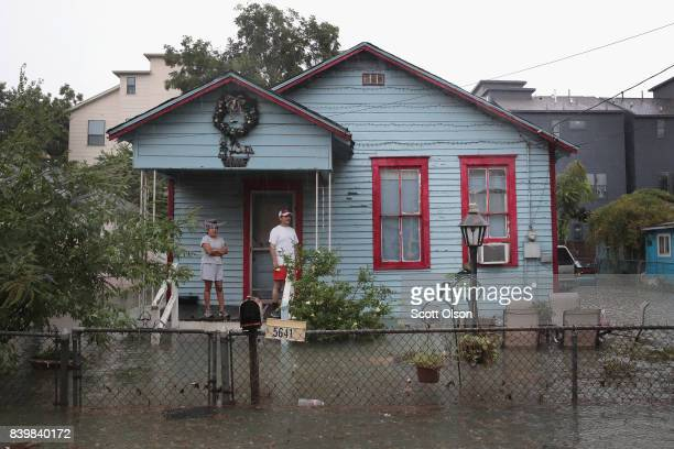 People on a porch watch as rain from Hurricane Harvey inundates the Cottage Grove neighborhood on August 27 2017 in Houston Texas Harvey which made...