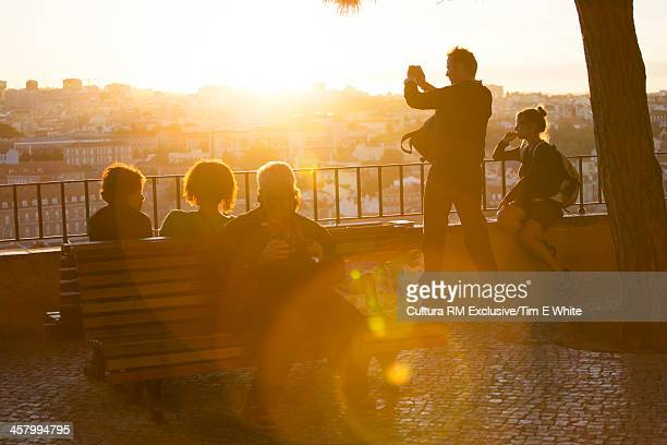 People on a terrace overlooking the city at sunset, Lisbon, Portugal