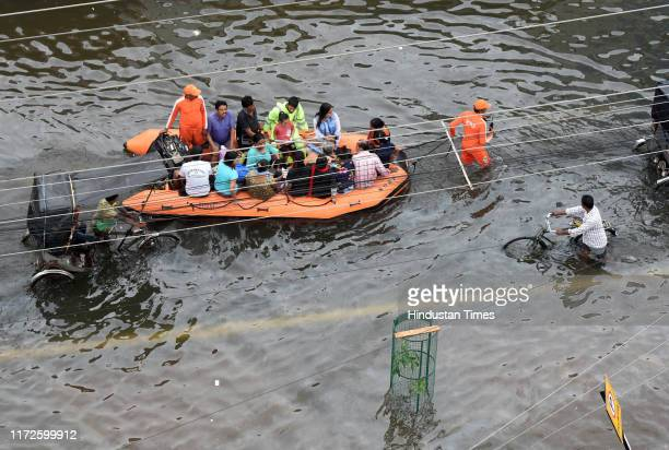 People on an NDRF boat make their way through waterlogged roads and streets attempting to move to safer locations after days of incessant rain on...
