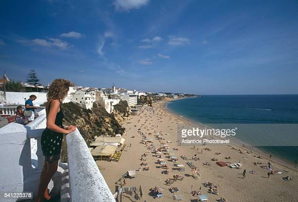 people on balcony overlooking beach - distrito de faro portugal imagens e fotografias de stock