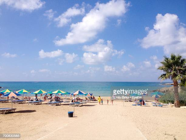 people on beach against blue sky - cyprus stockfoto's en -beelden