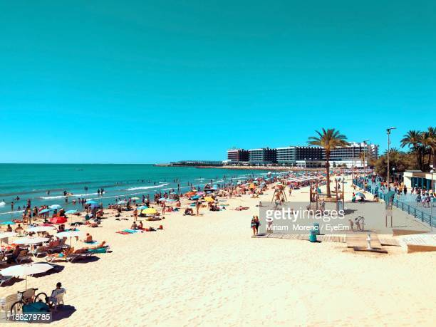people on beach against clear blue sky - alicante stock pictures, royalty-free photos & images