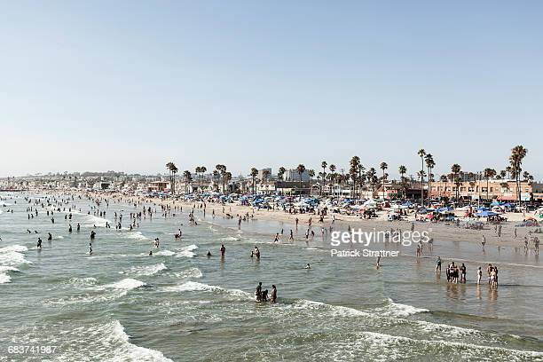 people on beach against clear sky, newport beach, california, usa - newport beach california stock photos and pictures