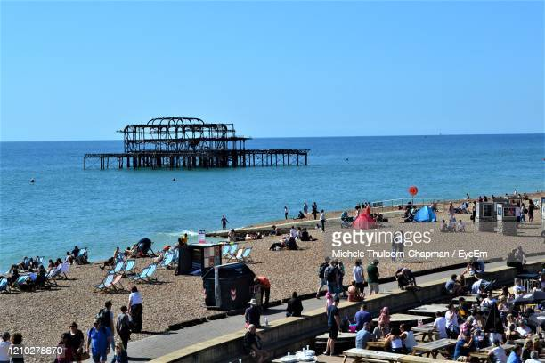 people on beach against clear sky - brighton stock pictures, royalty-free photos & images