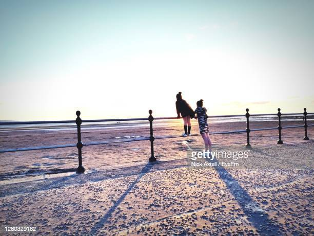 people on beach against clear sky - beach stock pictures, royalty-free photos & images