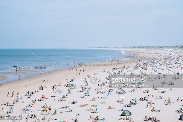 people on beach against sky - scheveningen stock pictures, royalty-free photos & images