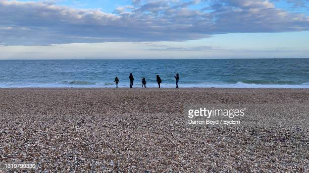 people on beach against sky - portsmouth england stock pictures, royalty-free photos & images
