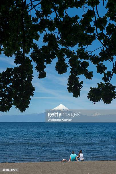 People on beach of Lake Llanquihue with Osorno Volcano in background in Frutillar a small town in the Lake District near Puerto Montt Chile