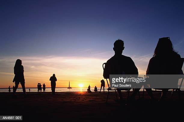 People on beach, silhouetted at sunset, Australia