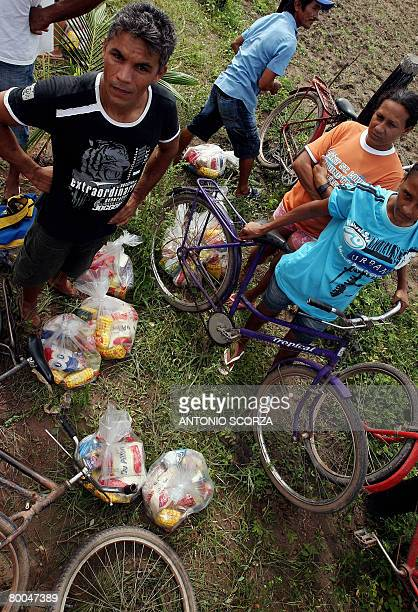 People on bike rest after receiving a basket of basic food at the entrance of the farm of Tailandia's mayor on February 28 2008 in Tailandia in the...