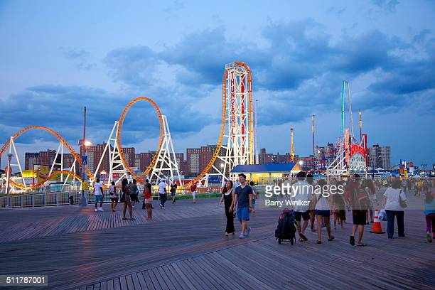 people on boardwalk near new roller coaster - coney island stock pictures, royalty-free photos & images