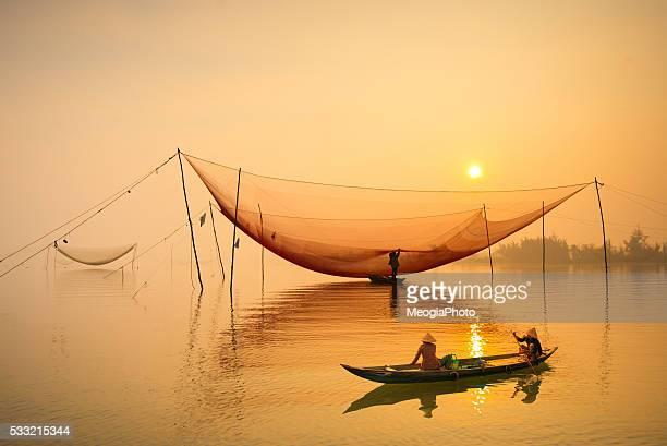 People on boat go to market in sunrise in Hoian, Vietnam