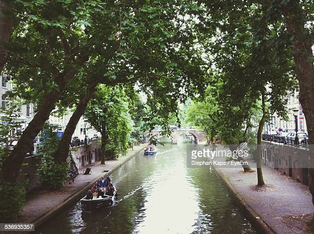 people on boats sailing in canal - utrecht stock-fotos und bilder