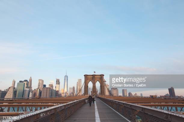 people on bridge against sky in city - brooklyn bridge stock pictures, royalty-free photos & images
