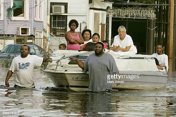 People on Canal St. Use a boat to get to higher ground as water began to fill the streets August 30, 2005 in New Orleans, Louisiana. Thousands of...