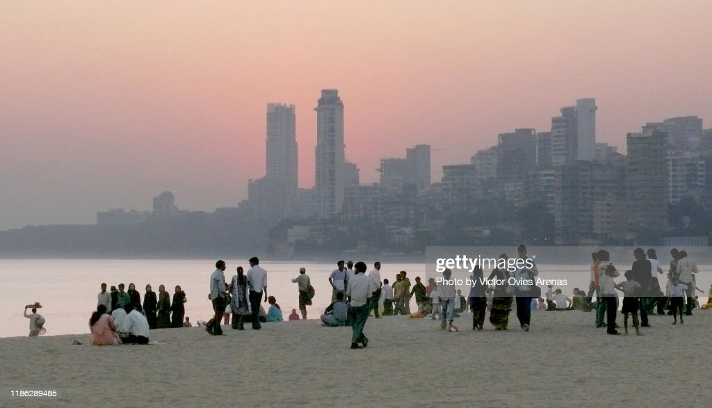 People on Chowpatty beach at sunset with Malabar hill in the background in Mumbai, Maharashtra, India : Foto de stock