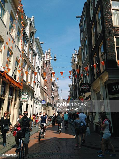 people on city street between buildings - haarlem stock photos and pictures
