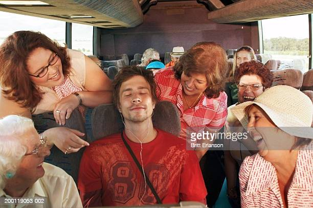 People on coach, women around man with eyes closed wearing headphones