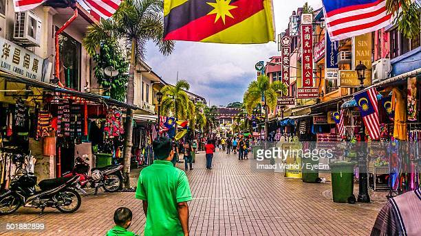 people on cobblestone street along stores - sarawak state stock pictures, royalty-free photos & images