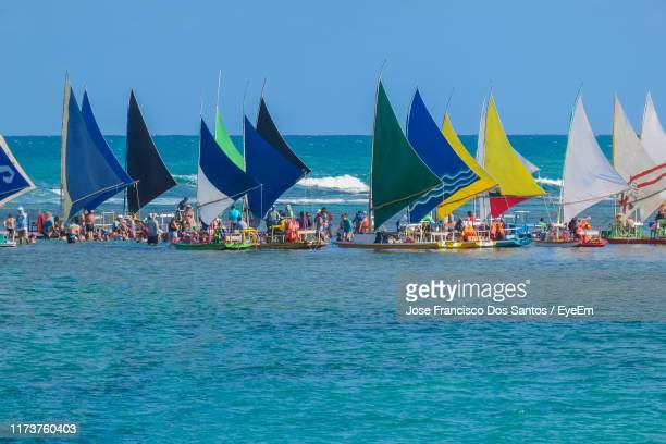 people on colorful sailboats in sea against clear blue sky - porto galinhas stock photos and pictures