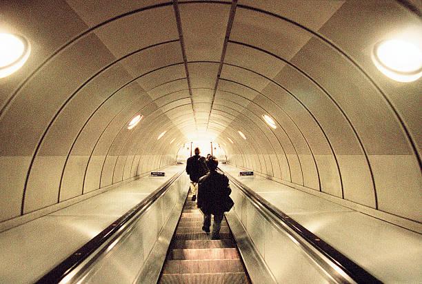 people on escalators in underground train station