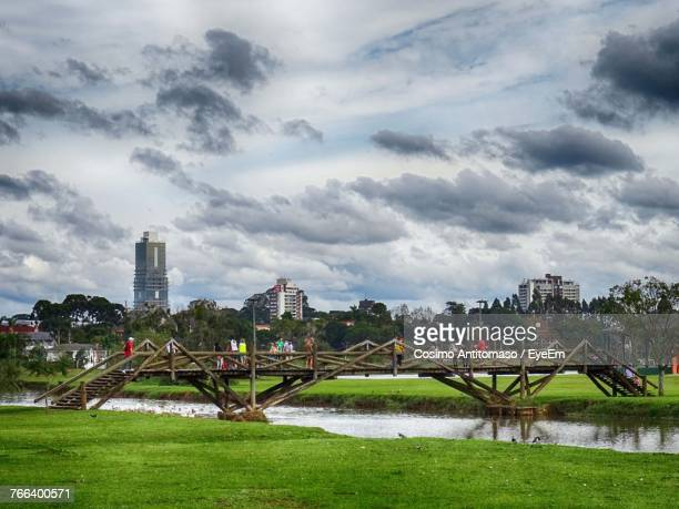 People On Footbridge Over River Against Cloudy Sky At Park
