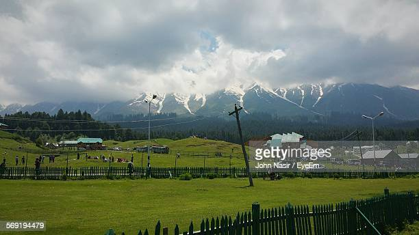 People on green landscape against Himalayas in Gulmarg