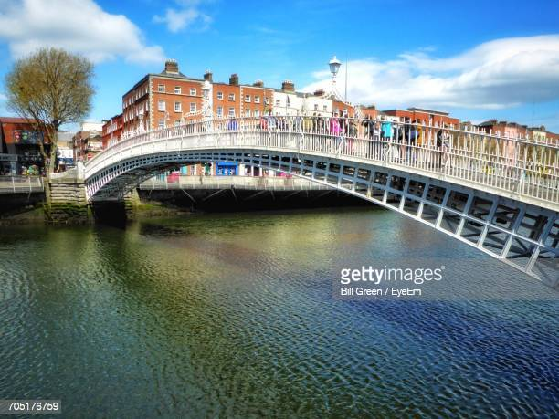 People On Hapenny Bridge Over River In City