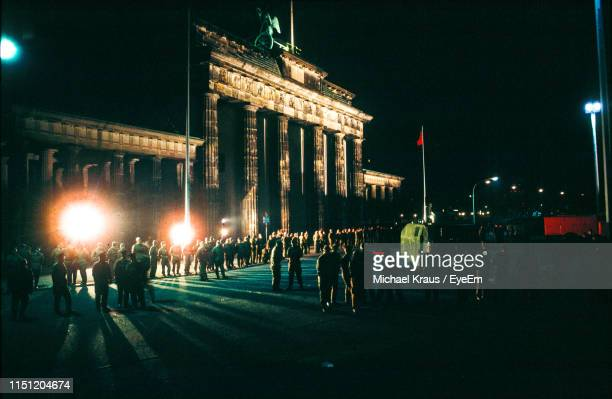 people on illuminated by historic building at night - east germany stock pictures, royalty-free photos & images