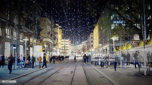 People On Illuminated City Street Amidst Buildings During Christmas