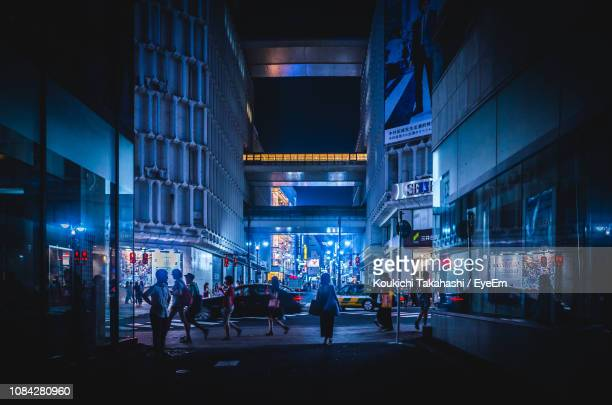 people on illuminated street amidst buildings in city at night - street stock pictures, royalty-free photos & images