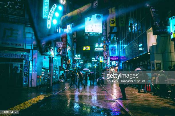 People On Illuminated Street At Night During Rainy Season