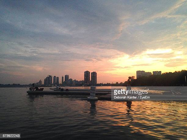 people on jetty over lake with city in background during sunset - tarrytown stock photos and pictures