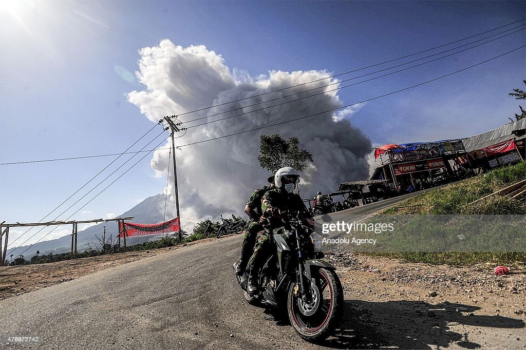 People on motorbike seen during Mount Sinabung spews pyroclastic flow from its crater visible from Tiga Pancur Village, Karo, North Sumatra, Indonesia on June 29, 2015. Around 10.000 people remain in temporary accommodation in the Indonesian region of North Sumatra as Mount Sinabung continues to spew volcanic ash, smoke and rock into sky.