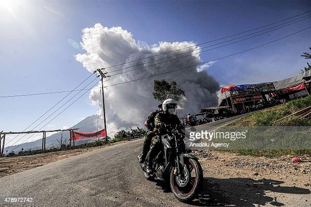 People on motorbike seen during Mount Sinabung spews pyroclastic flow from its crater visible from Tiga Pancur Village Karo North Sumatra Indonesia...