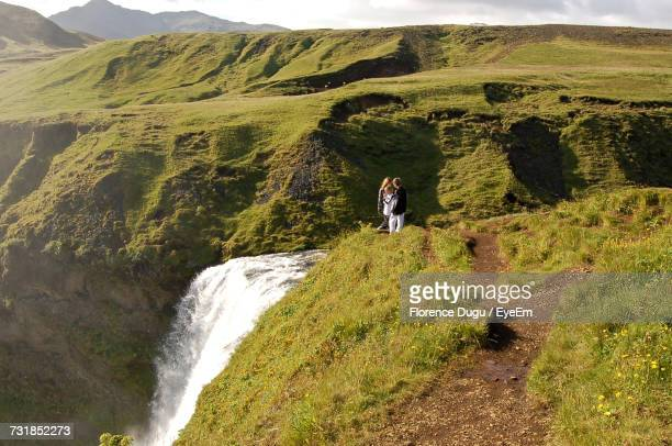 People On Mountain By Waterfall
