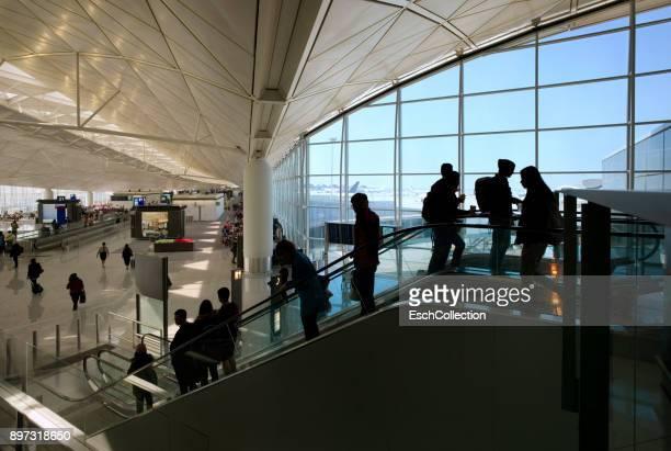 People on moving escalator at Hong Kong International Airport.