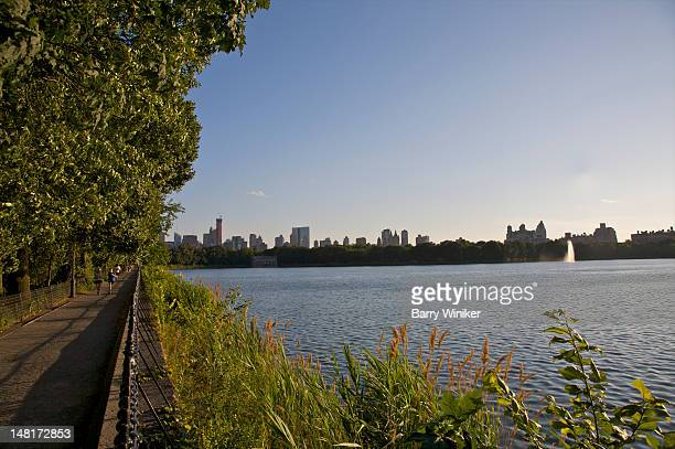 people on path near body of water and skyline. - central park reservoir stock pictures, royalty-free photos & images