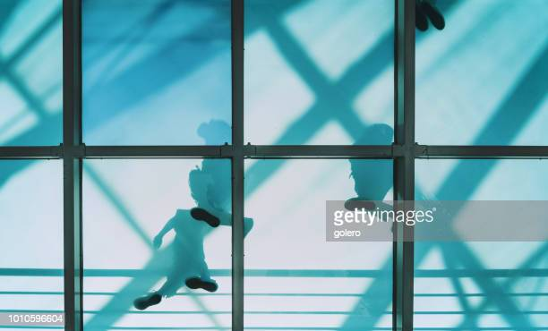 people on pedestrian glass bridge - man made structure stock pictures, royalty-free photos & images
