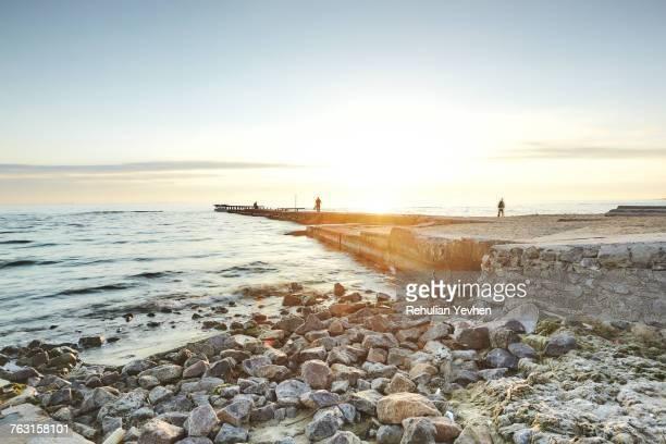 people on pier at sunset, odessa, odessa oblast, ukraine, europe - odessa ukraine stock photos and pictures