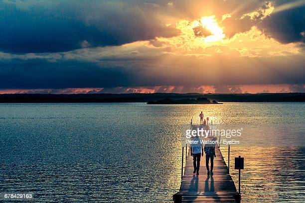 People On Pier Over River Against Cloudy Sky At Sunset
