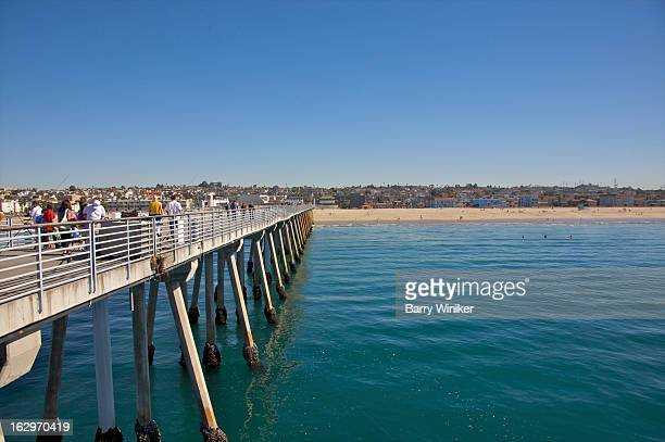 People on pier, pilings and calm waters.