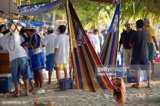 people on playa municipal beach, girl lying in hammock, zihuatanejo, guerrero, mexico - ixtapa zihuatanejo fotografías e imágenes de stock