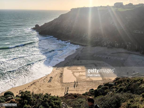 People on Porthcurno beach walk past a large scale sand portrait of Lieutenant Richard Charles GravesSawle one of a number from the project called...