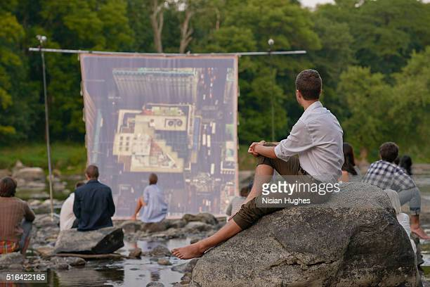 People on river sitting in front of movie screen